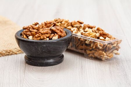 Peeled walnuts in stone bowl and plastic container on a gray wooden