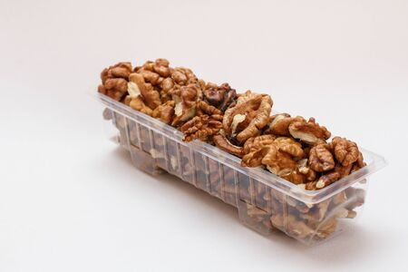 Plastic container with peeled walnuts on the white