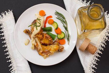 Rabbit legs baked in white wine with bechamel sauce on a ceramic plate with vegetables and rosemary. Фото со стока
