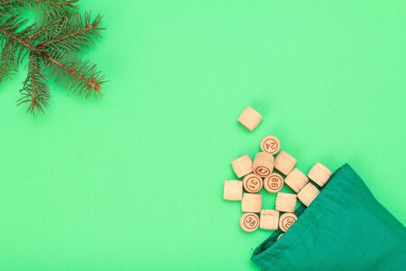 Board game lotto. Wooden lotto barrels with green bag, Christmas fir tree branch on green