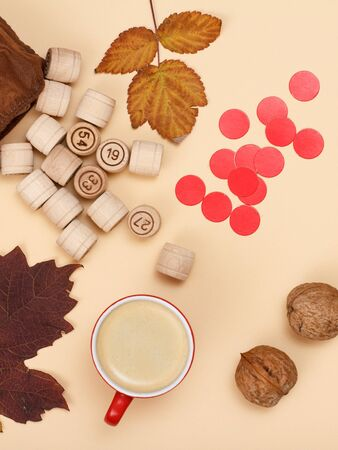 Wooden lotto barrels with open bag, dry autumn leaves, cup of coffee, red chips and walnuts on beige