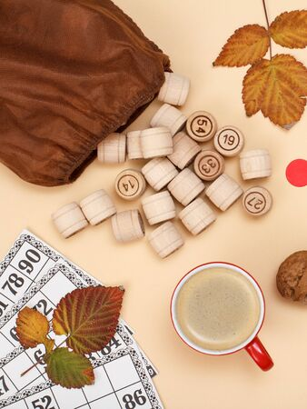 Wooden lotto barrels with open bag, dry autumn leaves, cup of coffee and game cards on beige