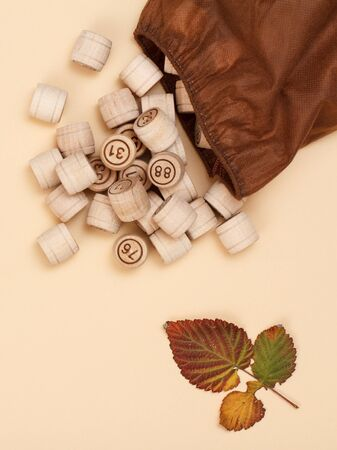 Wooden lotto barrels with open bag and dry autumn leaf on beige