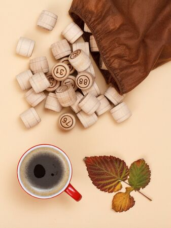 Lotto barrels with open bag, dry autumn leaf and cup of coffee on beige