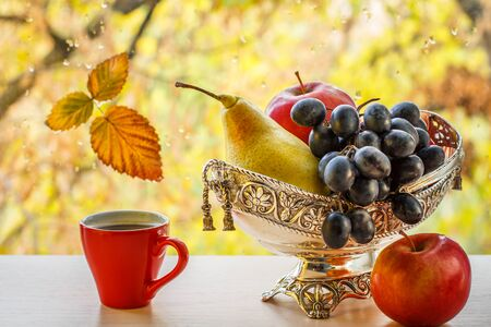 Cup of coffee, apple and metal vase with yellow pear and bunch of grapes. Zdjęcie Seryjne