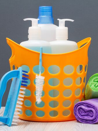 Plastic basket with bottles of dishwashing liquid, tile cleaner, detergent for microwave ovens and stoves. 版權商用圖片