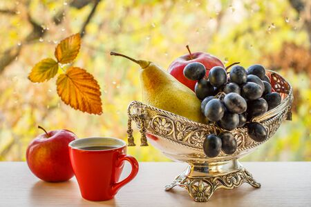 Cup of coffee, apple and metal vase with yellow pear and bunch of grapes