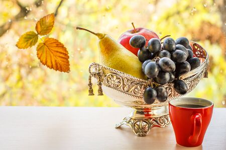 Cup of coffee and metal vase with yellow pear and bunch of grapes. Dry leaf on window glass with water drops and autumn trees outside Zdjęcie Seryjne