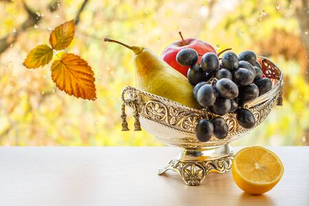 Metal vase with yellow pear, bunch of grapes and lemon. Zdjęcie Seryjne