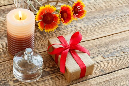 Perfume, gift or present box wrapped in kraft paper with red ribbon, burning candle and yellow flowers on wooden boards. Top view. Holiday concept.