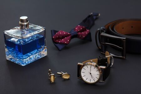 Cologne for men, bow tie, cufflinks, watch with a black leather strap and leather belt with metal buckle on black background. Accessories for men.