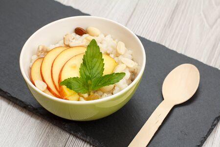 Porcelain bowl with sorghum porridge with fresh peach, cashew nuts and almond, wooden spoon on stone board. Vegan gluten-free sorghum salad with fresh fruits. 版權商用圖片