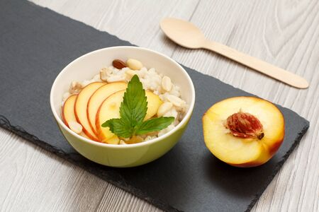 Porcelain bowl with sorghum porridge with cashew nuts and almond, a half fresh peach on stone board. Vegan gluten-free sorghum salad with fresh fruits. Top view.