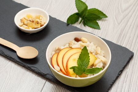 Porcelain bowl with sorghum porridge with fresh peach, cashew nuts and almond, wooden spoon and bowl with nuts on stone board. Vegan gluten-free sorghum salad with fresh fruits. 版權商用圖片