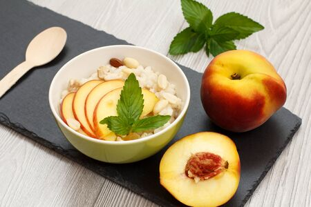 Porcelain bowl with sorghum porridge with cashew nuts and almond, whole fresh peach and a half one, wooden spoon on stone board. Vegan gluten-free sorghum salad with fresh fruits.