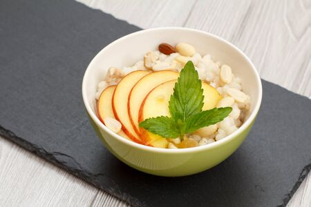 Porcelain bowl with sorghum porridge with fresh peach, cashew nuts and almond on stone board. Vegan gluten-free sorghum salad with fresh fruits.