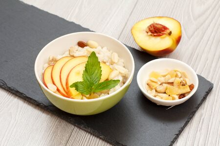 Porcelain bowl with sorghum porridge, peach, cashew nuts and almond, small bowl with nuts on stone board and a half fresh peach. Vegan gluten-free sorghum salad with fresh fruits. Top view.