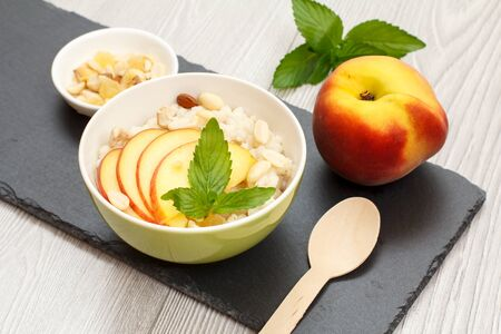 Porcelain bowl with sorghum porridge, peach, cashew nuts, almond, mint leaves, a fresh peach and a wooden spoon on stone board. Vegan gluten-free sorghum salad with fresh fruits. Top view.