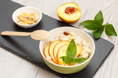 Porcelain bowl with sorghum porridge, peach, cashew nuts, almond, mint leaves and a wooden spoon on stone board. Vegan gluten-free sorghum salad with fresh fruits. Top view.