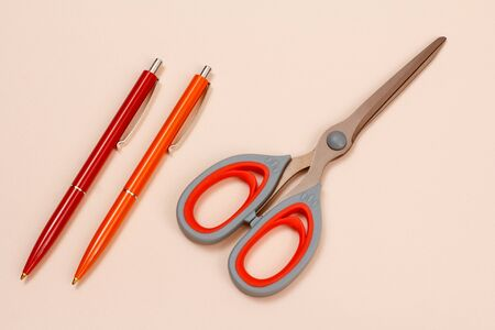 Two pens and scissors on a beige background. Top view. 版權商用圖片