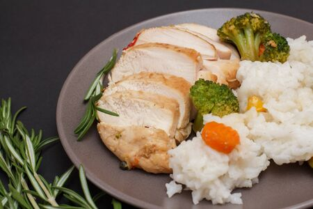 Baked chicken breasts or fillet on plate and rosemary on black