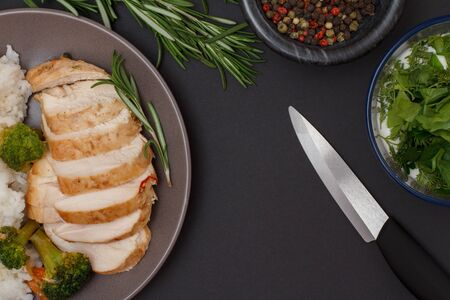 Baked chicken breasts or fillet on plate with rosemary, bowls with sauce and allspice berries and knife on black
