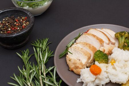 Baked chicken breasts or fillet on plate, rosemary, bowls with sauce and allspice berries on black Stock fotó