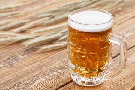 Glass mug of beer on old wooden boards with ears of barley Zdjęcie Seryjne