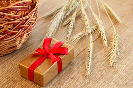 Gift box with wicker basket and spikelets of wheat