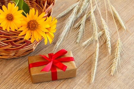 Gift box, wicker basket with flowers and spikelets of wheat on wooden boards. Top view.