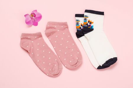 Two pairs of pink and white women socks and orchid flower on a colored Reklamní fotografie - 130153858