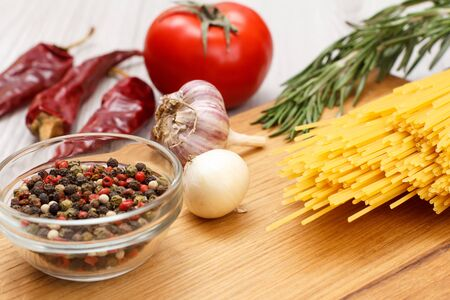 Pasta or spaghetti with ingredients for cooking meat or fish on a wooden cutting board.