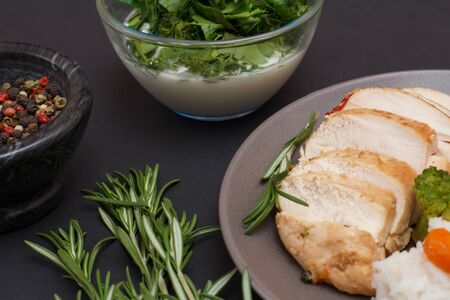 Baked chicken breasts or fillet on plate, rosemary, bowls with sauce and allspice berries on black background. Top view.