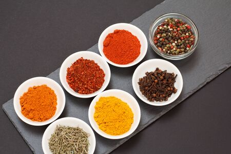 Colorful various ground spices, dry cloves and herbs in bowls on black stone cutting board. Top view.
