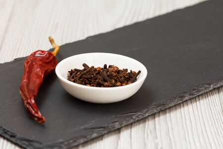 Whole cloves in a porcelain bowl and dry red pepper on stone cutting board.