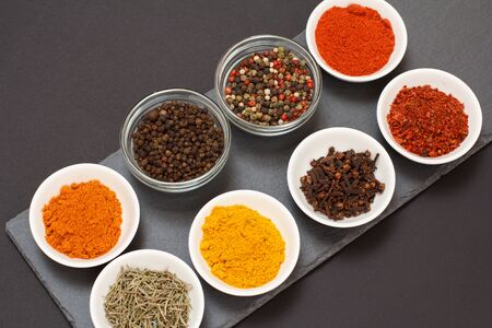 Colorful various ground spices, dry cloves and herbs in porcelain bowls on black stone board.