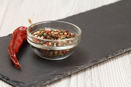 Whole allspice berries in a glass bowl and a dry red pepper on stone cutting board and wooden table.