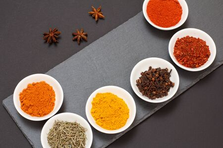 Colorful various ground spices, dry cloves and herbs in porcelain bowls on stone cutting board. Top view.