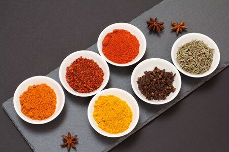 Colorful ground spices, dry cloves and herbs in porcelain bowls on black stone cutting board. Top view. Stock fotó