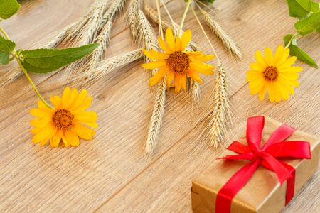 Spikelets of wheat, yellow flowers and gift box on wooden boards. Top view. Zdjęcie Seryjne