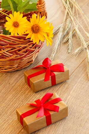 Gift boxes, wicker basket with flowers and spikelets of wheat on wooden boards.