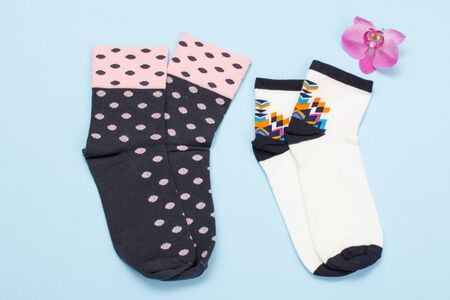 Two pair of black and white women socks, orchid flower on a blue Reklamní fotografie - 130153149