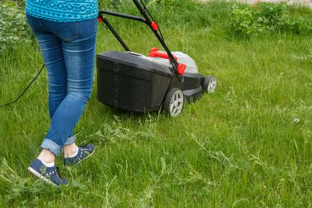 Female gardener is operating with lawn mower in the garden in summer day. Mower grass equipment. Mowing gardener care work tool.