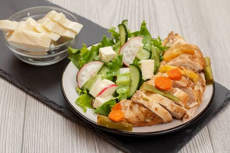 Plate with meat, fresh vegetable salad with cucumber and radish, glass bowl with cheese. Top view. Reklamní fotografie