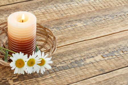 Burning candle and bouquet of chamomile flowers in wicker basket on wooden boards. Top view. Holiday concept. Stockfoto
