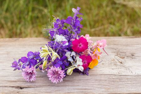 Bouquet of wildflowers on old wooden board with natural background.