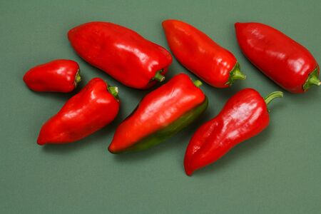 Fresh red bell peppers on green background. Top view.