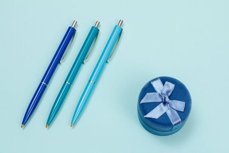 Three automatic pens and gift box on a blue background. Top view.