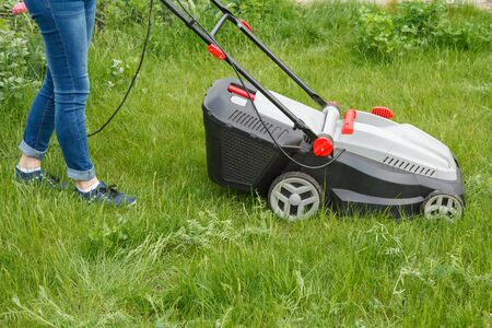 Female gardener in blue jeans is operating with lawn mower in the garden in summer day. Mower grass equipment. Mowing gardener care work tool. Banque d'images