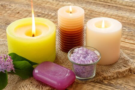 Soap, burning candle, bowl with sea salt and lilac flowers on wooden boards. Spa products and accessories.